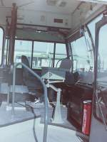 MAN SG 192/142203/wagen-164-ein-blick-durch-die Wagen 164. Ein Blick durch die offene Tür zeigt den Arbeitsplatz im Gelenkbus an einem seiner letzten Arbeitstage, am 23.09.83. Auf diesem Foto ist gut der Schalthebel zu erkennen (Wagen 165 und 164 waren die letzten Gelenkbusse mit Schaltgetriebe) und die erhöhte letzte Stufe in den Fahrgastraum. Bei allen Bussen dieses Typ fand man vorne neben der Heizung den Feuerlöscher. Die Heizung vom Typ Webasto, die auch als Standheizung arbeitet, war allerdings nicht geeignet, um im Winter wohlige Wärme im Bus zu verbreiten. In den Gelenkbussen bestand eine zusätzliche Heizstrecke, die hier hinter dem Fahrersitz zu erkennen ist. In den Solowagen spannten die Fahrer im Winter schon mal eine Art Vorhang von der Rückwand der Abtrennung hinter dem Fahrer, vorbei am Zahltisch zum äußeren Teil der Heizung, um die Wärme in ihren Fußbereich zu lenken und die einströmende kalte Luft bei geöffneten Türen abzuhalten. Über dem Kopf des Fahrers war ein kleiner Ventilator angebracht, der im Sommer eine leichte Brise erzeugen konnte. Daneben ist der Cassettenrekorder zu erkennen, der die Haltestellenansagen abspielte. Die Cassetten waren so besprochen, dass nach einer Ansage eine Pause folgte. Dann schaltete sich der Rekorder ab. Daneben befindet sich eine Halterung, in der eine Kladde abgelegt wurde, in der die Fahrer an den Endstellen u.a. die jeweiligen Endnummern der Fahrscheinblöcke eintrugen. So konnten die Kontrolleure feststellen, ob Fahrgäste evtl. keinen neuen Fahrschein gelöst hatten. In einem Fach über dem Ventilator war der Erste-Hilfe-Kasten untergebracht. Daneben befand sich eine weitere Halterung in der der Fahrzeugschein des Busses klemmte. Dann folgte ein weiteres Fach für die zu benutzenden Fahrtenschreiberdiagrammscheiben. Der Fahrersitz war bei den Bussen dieser Baujahre ausschließlich mechanisch gefedert und musste per Stellschraube auf das Gewicht des jeweiligen Fahrers eingestellt werden. Erst später wurde die Sitze l